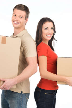 Beautiful young couple standing close to each other. man and woman smiling at camera while holding cardboard boxes photo
