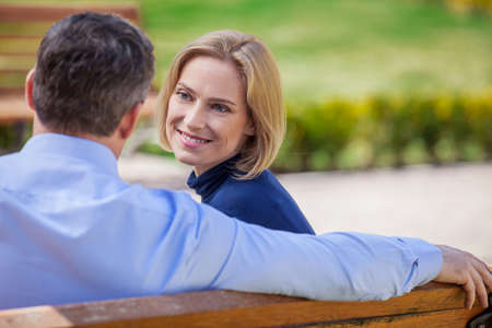 Adult smiling couple looking on each other sitting on bench. beautiful elegant mid age couple daydreaming outdoors photo