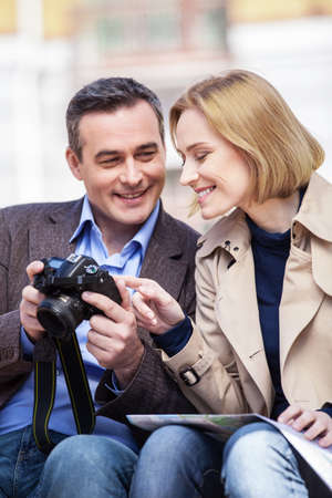 beautiful elegant mid age couple resting outdoors. man holding camera and showing pictures to blond woman photo