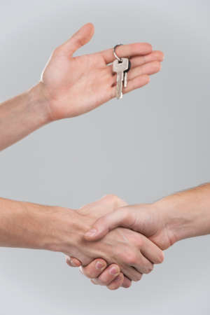 accommodation broker: Two businessperson shaking hands on grey background. only hands seen and key given on finger Stock Photo
