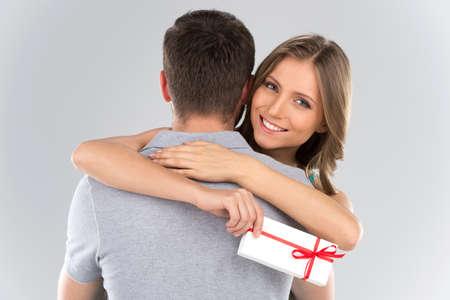 Junges Paar umarmt mit verpacktes Geschenk. Frau umarmt Mann und mit Band Geschenk hält
