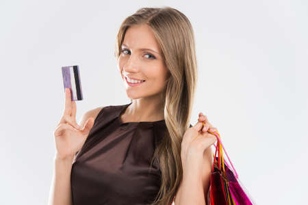 spender: Portrait of young beautiful smiling woman with credit card. Brunette girl and many colorful shopping bags isolated on white background
