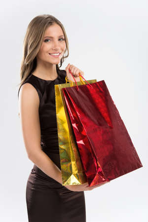 short sale: Shopping woman holding bags isolated on white background. Side view of girl with colorful bags looking into camera