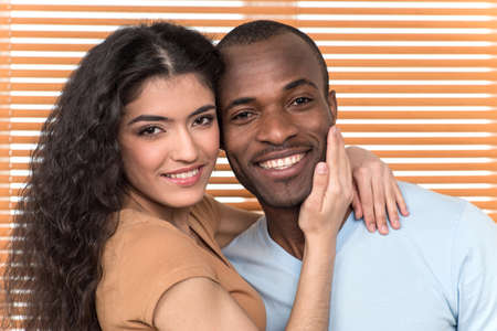 blackman: pretty couple hugging and looking into camera. African man and Hispanic woman standing close before shutters