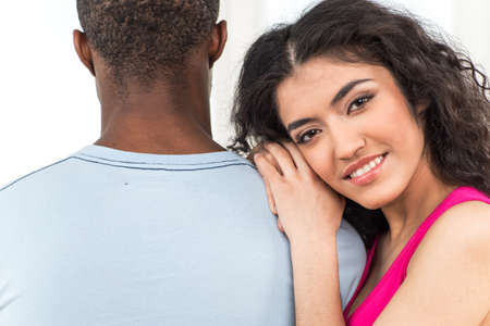 blackman: pretty woman leaning on man shoulder and smiling on white background. African man standing with his back to camera Stock Photo