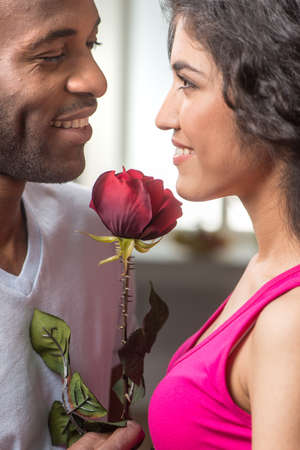 inlove: Man offering rose to his pretty girlfriend. african man looking at indian woman and smiling Stock Photo