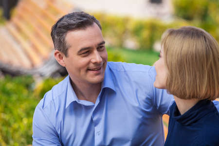 happy couple outside talking and looking at each other. portrait of man and woman having romantic time photo