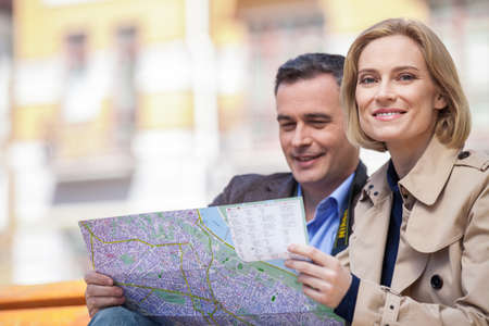 looking into camera: beautiful elegant mid age couple resting outdoors. man holding map while blond woman looking into camera
