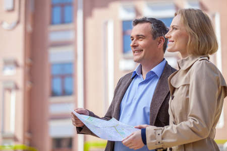 mid age: beautiful elegant mid age couple standing outdoors. side view of smiling woman holding map and looking ahead Stock Photo