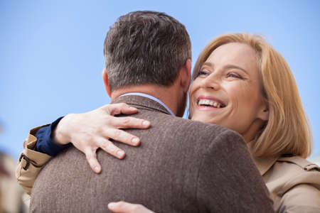 faithful: back view of man hugging happy woman outside. Smiling blond woman embracing man outside
