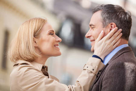 Portrait of amorous couple touching faces and laughing. blond woman looking at man and smiling Stock Photo