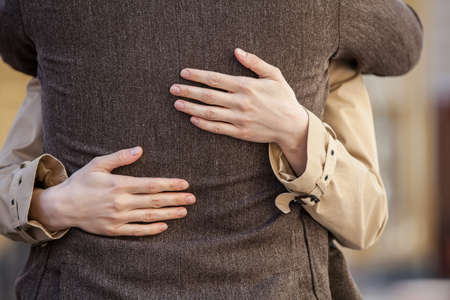 road to love: adult couple standing on street and hugging. closeup of woman hands hugging man outside Stock Photo