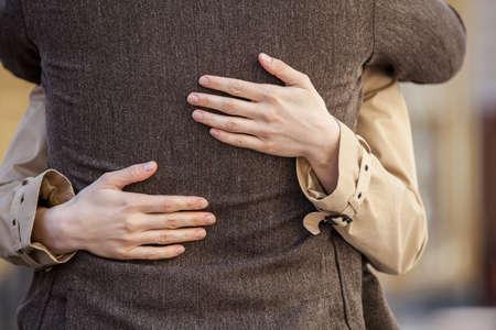 volwassen paar staande op straat en knuffelen. close-up van de vrouw handen knuffelen man buiten Stockfoto