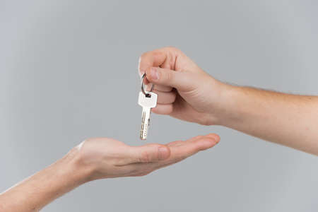 hand key: Male hand holding key and handing it over to another person. Handing key from one hand to another on grey background Stock Photo