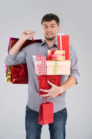 christmas bonus: young guy holding stack of boxes. surprised male making scared face on grey background Stock Photo