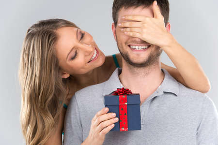 gift background: romantic woman covering her boyfriends eyes. girl standing behind man with gift isolated on grey background