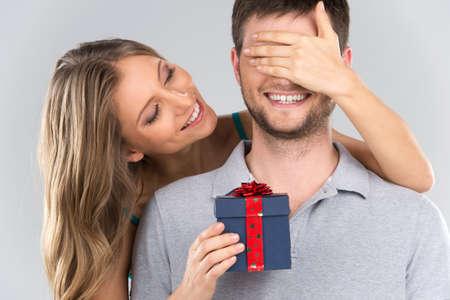 romantische vrouw die de ogen van haar vriend. meisje dat zich achter de man met cadeau geïsoleerd op grijze achtergrond Stockfoto