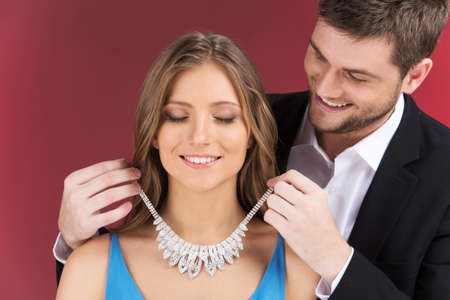 Man attaching necklace to girls neck. man standing behind woman with eyes closed and jewelry