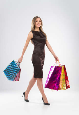 Shopping woman walking with bags isolated on white background. Happy shopping girl with colorful bags looking into camera photo