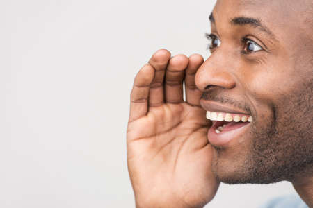 gossip: Handsome young men gossiping while standing isolated on white. Closeup portrait of black african young man whispering