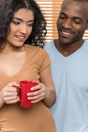 pretty woman holding cup and man looking at her. African man and Hispanic woman standing close before shutters Stock Photo