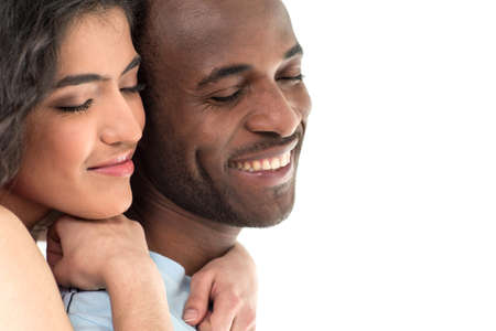 pretty woman hugging man and smiling on white background. African man and Hispanic woman standing with eyes closed