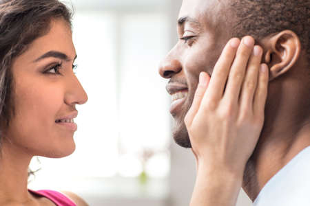 Portrait of beautiful couple looking at each other. closeup of african man smiling at indian woman photo