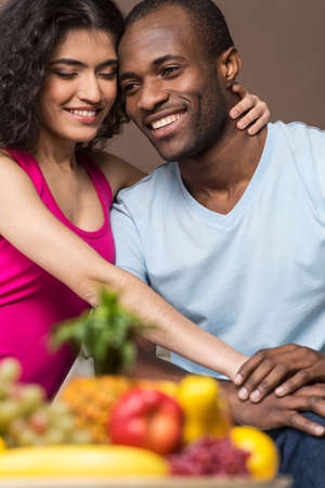thirty���s: happy African American man and woman. Couple in their thirties sitting at home together cuddling & laughing. Stock Photo