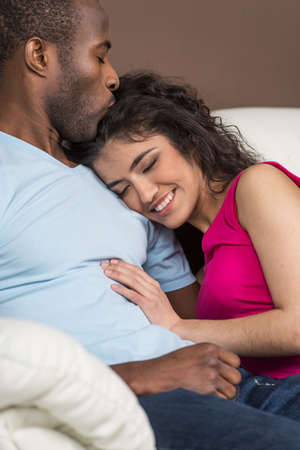 Portrait of African American couple on sofa. woman lying on man chest and man kissing woman head photo