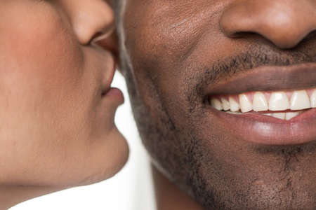 kissing lips: woman kissing black man on cheek. closeup portrait of african man smiling