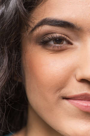 half and half: Closeup of half face of young fresh woman. Closeup shot of beautiful indian womans half face Stock Photo