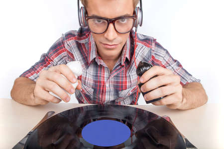 Young man working as dj with ear-phones and glasses.  photo