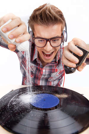 Young man working as dj with ear-phones and glasses. closeup photo of mad man pouring salt and paper on disk photo