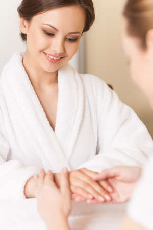 handcare: Woman in nail salon receiving manicure by beautician. Dermatologist consulting her client in bath robe on hand care Stock Photo