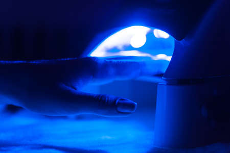 Manicure in process using Uv lamp for nails. client woman drying nails at manicurist salon in dark