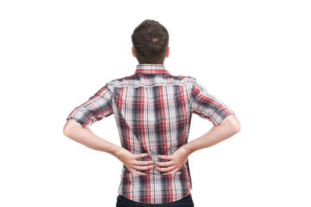 low back: young man holding his hand to his aching back. Stock Photo