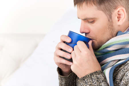 wärmflasche: Nahaufnahme auf Mann auf dem Sofa trinken heißen Tee.