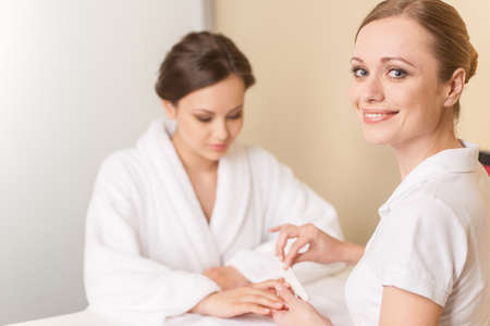 Close-up of beautician hand filing nails of woman in salon. manucurist women sitting in spa salon and looking at camera
