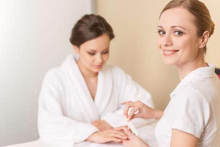 Close-up van schoonheidsspecialiste de hand indienen spijkers van de vrouw in de salon. manucurist vrouwen zitten in de spa salon en kijken naar de camera