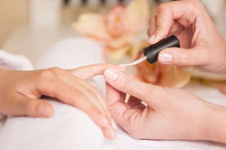 Vrouw in nagelsalon het ontvangen van manicure schoonheidsspecialiste. close-up van vrouwelijke hand rusten op het witte doek