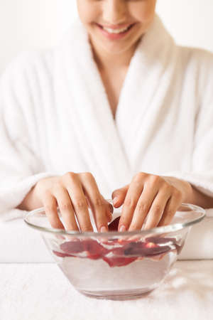 Woman hands in glass bowl with water on white towel. front view of girl holding her beautiful hands in water and smiling