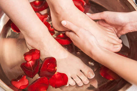 feet washing: Closeup photo of female feet at spa salon on pedicure procedure. Female legs in water decoration flowers and getting massage