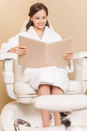 hairdress: Young woman receiving pedicure in hairdressing salon. Woman with hair color samples sits in hairdress salon Stock Photo
