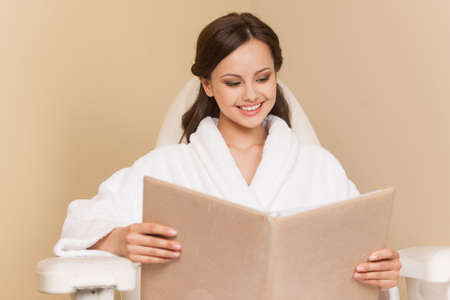 hairdress: Young woman receiving pedicure in hairdressing salon. Woman sits in hairdress salon and reading