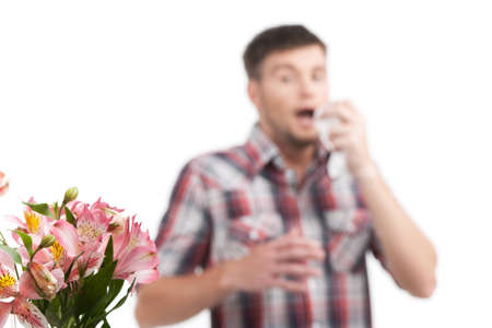 allergy man blowing his nose in tissue paper. Man blowing his nose isolated on white background photo