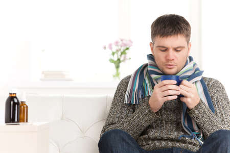 flu shot: man on sofa drinking hot tea. young man holding cup on sofa in living room Stock Photo