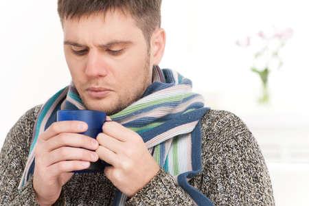 wärmflasche: Großansicht auf Mann auf Sofa trinken heißen Tee. junger Mann mit Tasse auf Sofa im Wohnzimmer