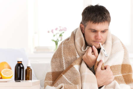 Man with cold sitting on sofa with thermometer in mouth. Man at home sick with flu, taking his temmperature