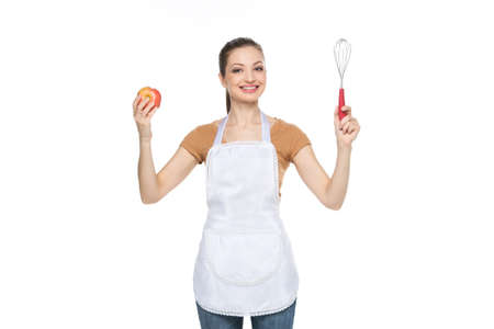 young housewife holding red apple. beautiful brunette on white background holding mixer photo
