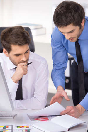 two businessmen having discussion in office. Two businessmen looking at charts and graphs on table photo